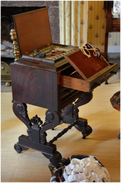 The work table/writing desk shown with the writing stand in position. The top lid is open showing where ink, pens, notebooks, and other accessories would be stored. The notebooks which remain with the sewing table contain Sarah Jackson's memoranda and Bible verses.
